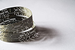 Strips of old punched tape on a white surface Stock Photography