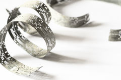 Strips of old punched tape on a white surface Stock Photos