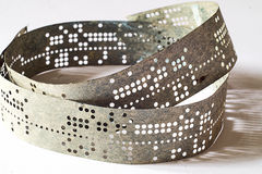 Strips of old punched tape on a white surface Royalty Free Stock Image