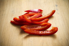 Strips of organic red pepper. Strips of fresh organic red pepper on a cutting board Stock Image