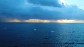 Aerial view rain over the sea in the afternoon in Sri Lanka. Strips of rain descend on the sea surface, closing the rays of the sun in Sri Lanka stock footage
