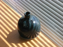 Strips of sunlight and shadow on the ceramic vase Royalty Free Stock Photos