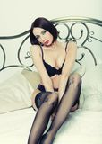 Striptease dancer on bed. Royalty Free Stock Photos