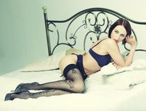 Striptease dancer on bed. Royalty Free Stock Image