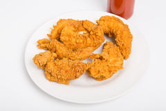 Strisce del pollo in piatto bianco con la bottiglia di salsa piccante Fotografia Stock Libera da Diritti