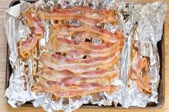 strisce di bacon al forno su stagnola sulla cottura dello strato Fotografia Stock
