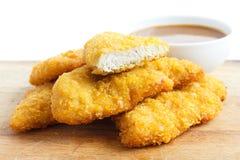 Strisce dorate del pollo fritto sul bordo di legno fotografie stock libere da diritti