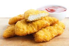 Strisce dorate del pollo fritto sul bordo di legno immagini stock libere da diritti