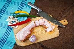 Strisce e peperoncini di bacon sul tagliere Fotografie Stock