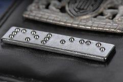 Striscia del Braille su una scheda della garanzia della polizia Fotografia Stock