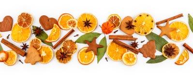 Striscia delle arance secche, limoni, mandarini, anice stellato, bastoni di cannella e pan di zenzero, isolati su bianco Fotografia Stock