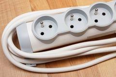 Striscia di corrente elettrica con il commutatore di accensione sul pavimento di legno Fotografia Stock Libera da Diritti