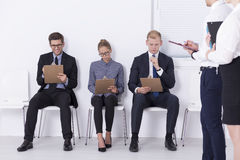 Strive for a place in the team. Shot of applicants sitting on chairs and taking a pre-employment screening Stock Photo