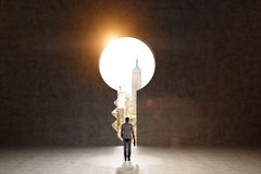 Striving for a bright future. A man with a folder standing in front of a huge keyhole, New York and light seen through it. Black background. Back view.  Concept Royalty Free Stock Image