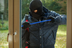 Striving to open. A burglar striving to open a window to a house Stock Photography