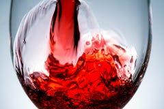 Ström av vin som hälls in i ett exponeringsglas som plaskar, färgstänk, Arkivfoton