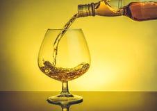 Strömende Schallkanone des Kellners Weinbrand im eleganten typischen Kognakglas auf Tabelle Stockfotografie