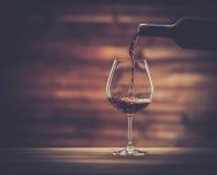 Strömender Rotwein in das Glas Stockfotos
