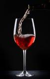 Strömender Rotwein in ein Glas Stockfotos
