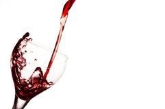 Strömender Rotwein im Glas Stockfotografie