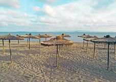 Stro behandelde paraplu op het strand met turkoois water op de achtergrond stock fotografie