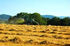 Stro het in balen verpakken tractor op tarwegebied. Stock Foto