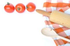Strofinaccio a quadretti, cucchiaio, pomodori e matterello isolati su bianco Fotografia Stock Libera da Diritti