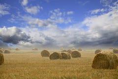 Strohballen auf Ackerland mit bewölktem Himmel Stockfotografie