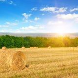 Strohballen auf einem Weizenfeld und einem Sonnenaufgang auf Himmel lizenzfreie stockfotos