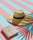 Strohhut, altes Buch und Schatten von tropischen Palmblättern auf hellem rosa Hintergrund der blauen Streifen Minimales Sommerkon stockbild
