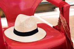 Strohhut auf einem roten Plastikstuhl Lizenzfreie Stockfotografie