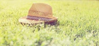 Strohhut auf Gras während der Sommersaison Stockbild