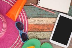 Strohhut, Lichtschutz, Pantoffel, Tablette und Sonnenbrille auf hölzernem Hintergrund Sommerferienrückseite Stockfotos
