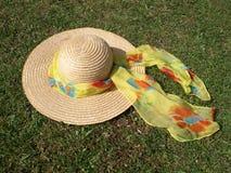 Strohhut mit hellem Schal im Sonnenschein. Lizenzfreie Stockfotos