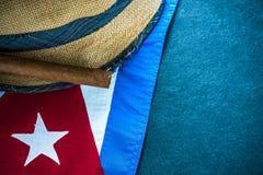 Strohhut mit kubanischer Zigarre und Kubanerflagge Stockbild
