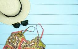 Strohhut, Sonnenbrillen, Sommerkleid auf hellgrünem hölzernem backg stockfoto