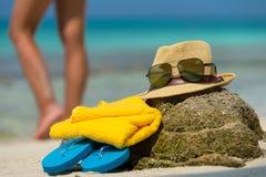 Strohhut, Tuchstrandsonnenbrillen und Flipflops auf einem tropischen Stockfotos
