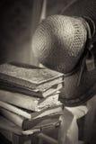 Strohhut und alte Bücher auf Stuhl Stockfoto