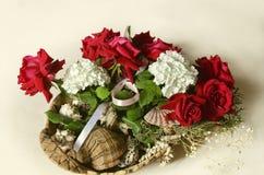 Strohkorb mit einem Blumenstrauß von roten Rosen, von weißen Hortensien und von Eukalyptus verzweigt sich mit Seeoberteilen Stockbilder