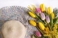 Strohoed met boeketten van tulpen Stock Foto's