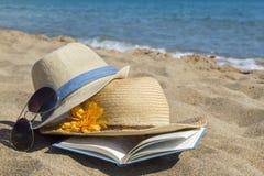 Strohoeden, zonnebril en een boek op het strand De vakantie van de zomer Stock Fotografie