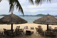 Strohregenschirm auf dem Strand Stockbilder