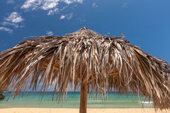 Strohregenschirm auf einem tropischen Strand Lizenzfreies Stockfoto