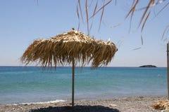 Strohregenschirm auf Strand Lizenzfreie Stockbilder
