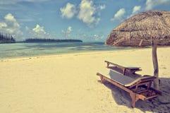 Strohregenschirm und Holzstühle auf einem Strand, Insel von Kiefern, Neukaledonien Stockfotografie