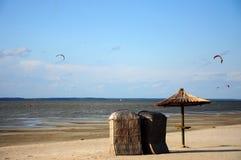 Strohregenschirm- und -strandbett mit dem Kitesurfing Lizenzfreie Stockfotos