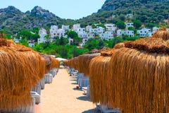 Strohregenschirme auf dem Strand Lizenzfreie Stockfotografie