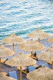 Strohregenschirme auf dem Strand lizenzfreie stockfotos