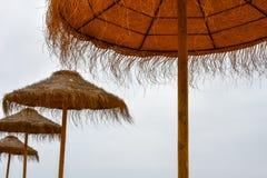 Strohregenschirme gegen einen neutralen Himmelhintergrund Stockfotografie