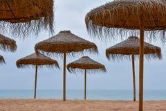 Strohregenschirme mit hölzernem Pfosten auf einem sandigen Strand Stockfotografie